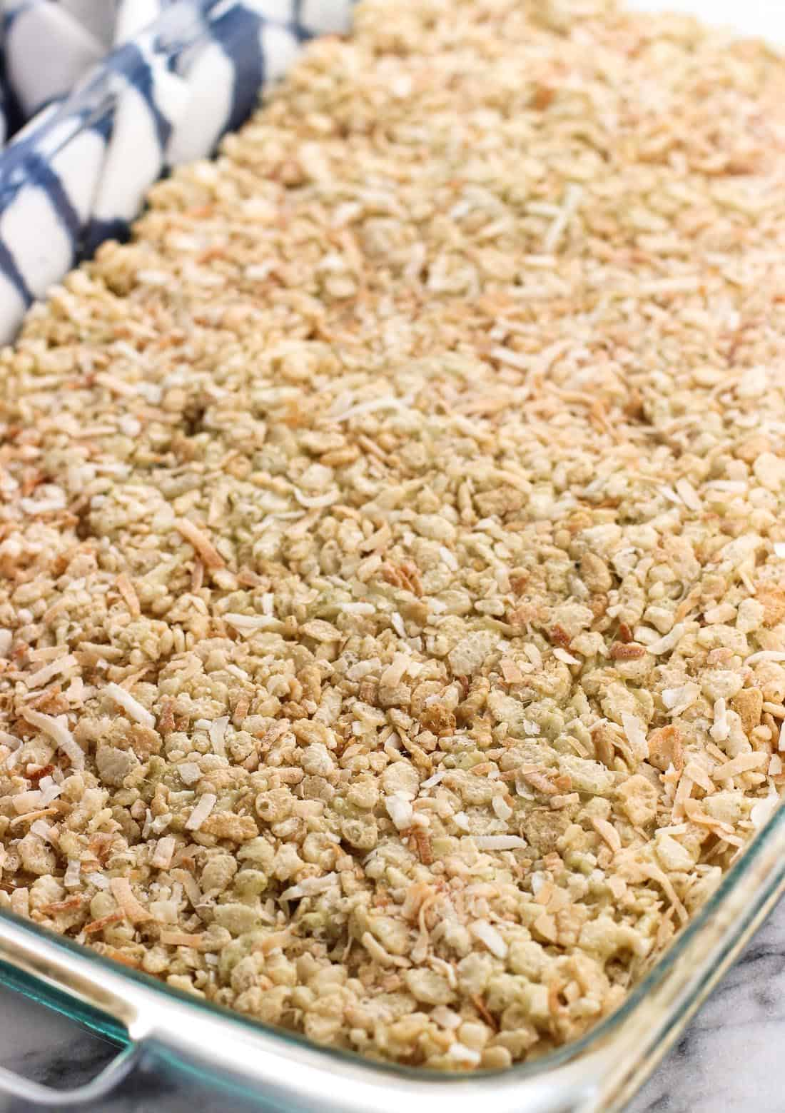 The rice crispy mixture pressed evenly into a rectangular glass dish.