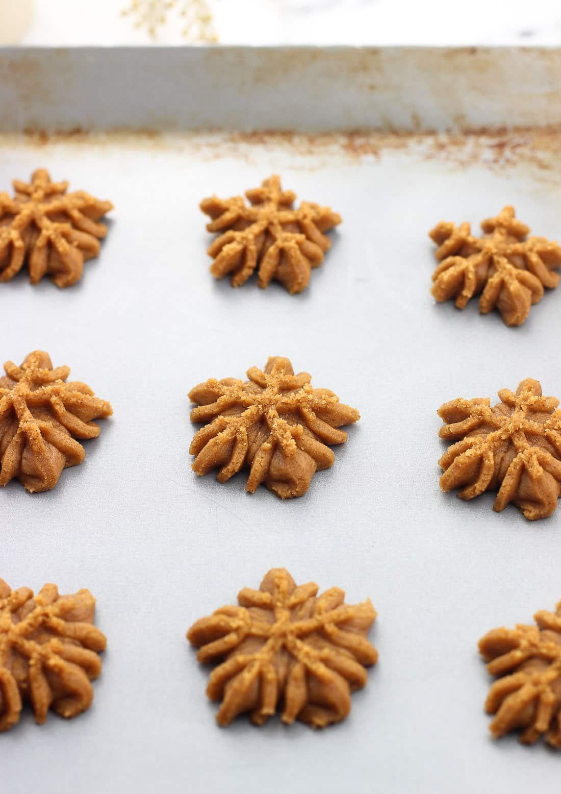Snowflake-shaped cookies on a metal cookie sheet before being baked