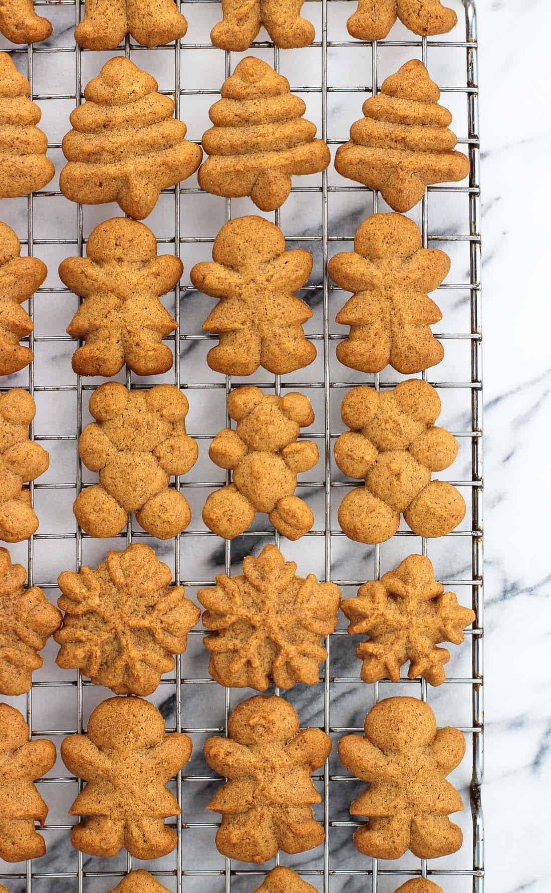 An overhead shot of a variety of gingerbread spritz cookies (a Christmas tree, a gingerbread woman, a teddy bear, and a snowflake) on a wire rack