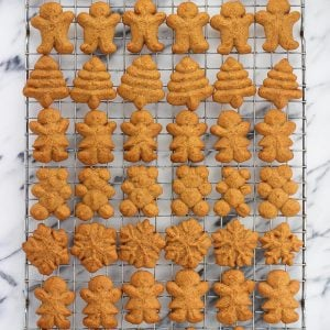 A variety of shaped gingerbread spritz cookies on a wire rack.