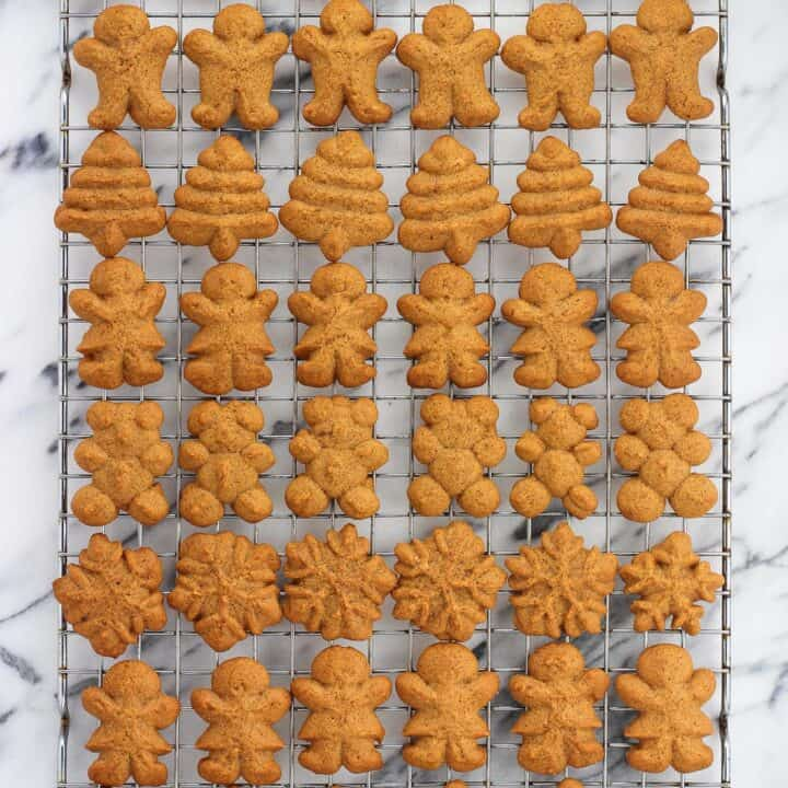 An overhead picture of rows of differently shaped cookies on a wire cooling rack