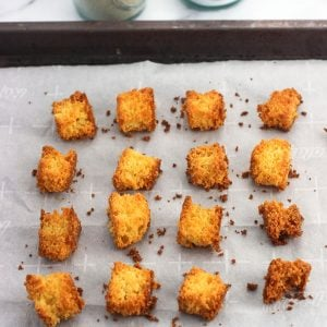 Sixteen cornbread croutons on a parchment-lined baking sheet with salt and pepper shakers in the background