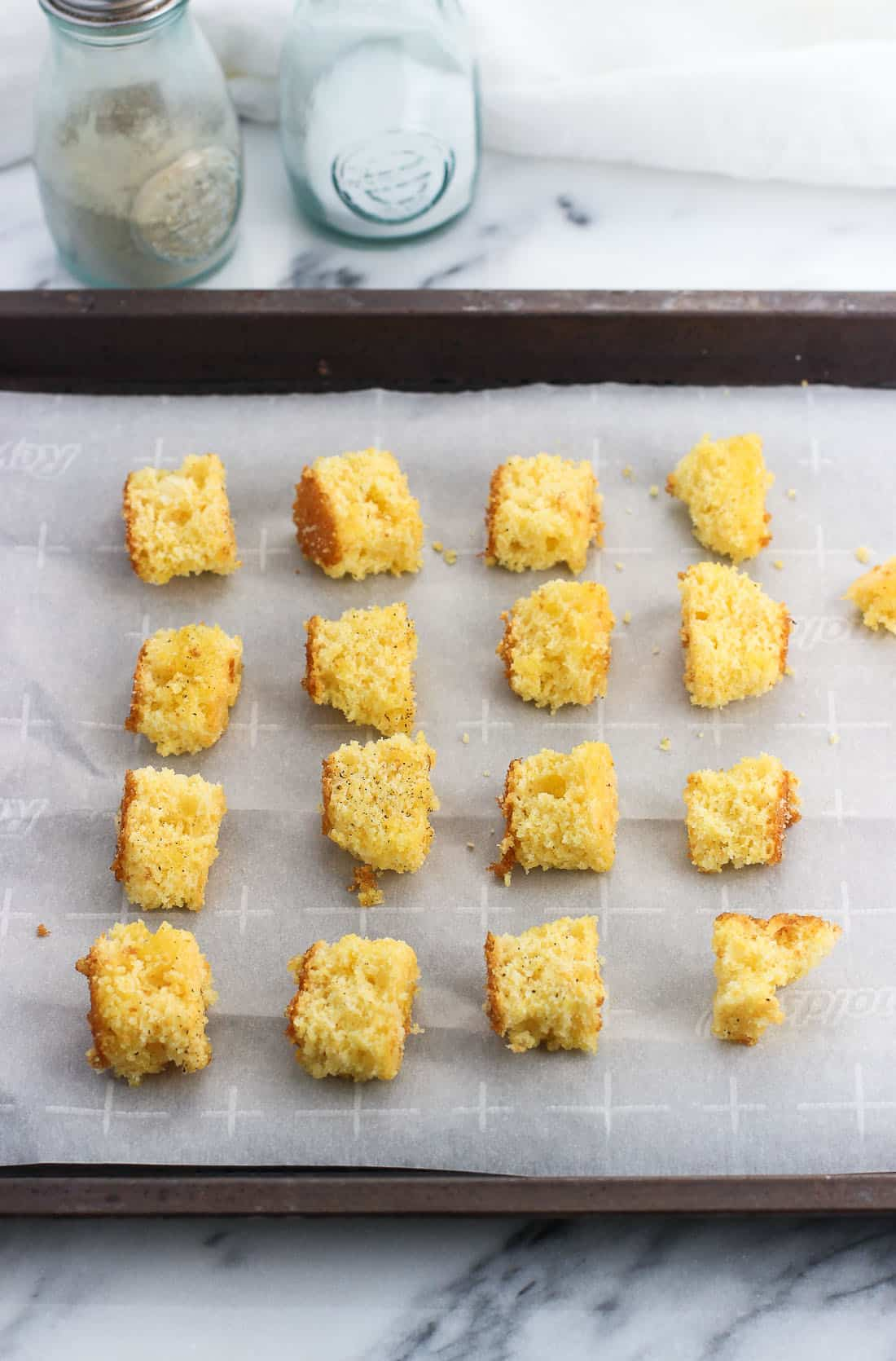 Sixteen pieces of small cornbread cubes on a parchment-lined baking sheet before baking