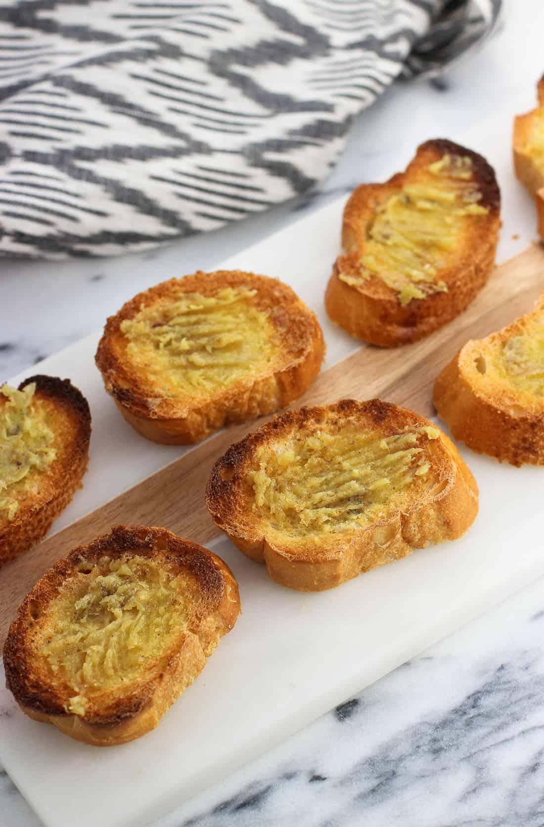 Roasted garlic spread onto toasted crostini.