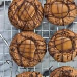 An overhead picture of thumbprint cookies drizzled with chocolate on a metal wire cooling rack