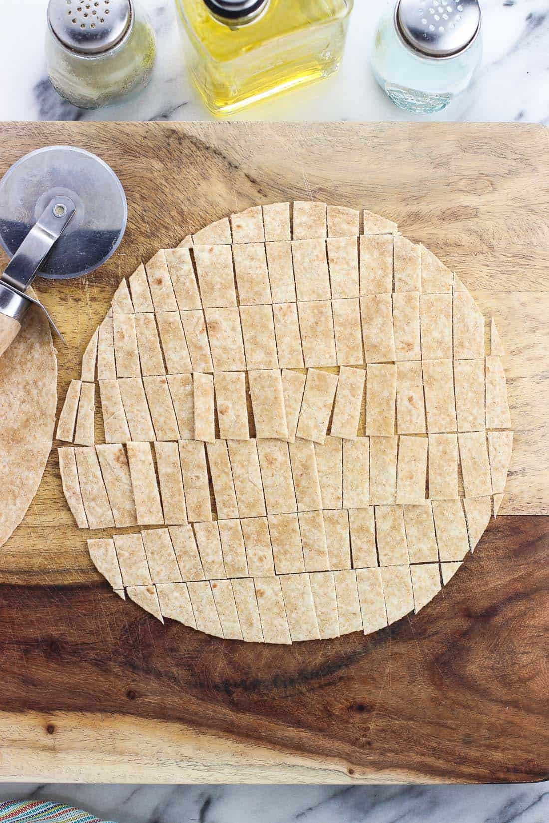 Learn how to make tortilla strips in the oven with this simple method. They crisp up SO well while being oven-baked, and can be seasoned just how you like them for topping salads, soups, chilis, and more. I like to use whole wheat tortillas for a healthier option!