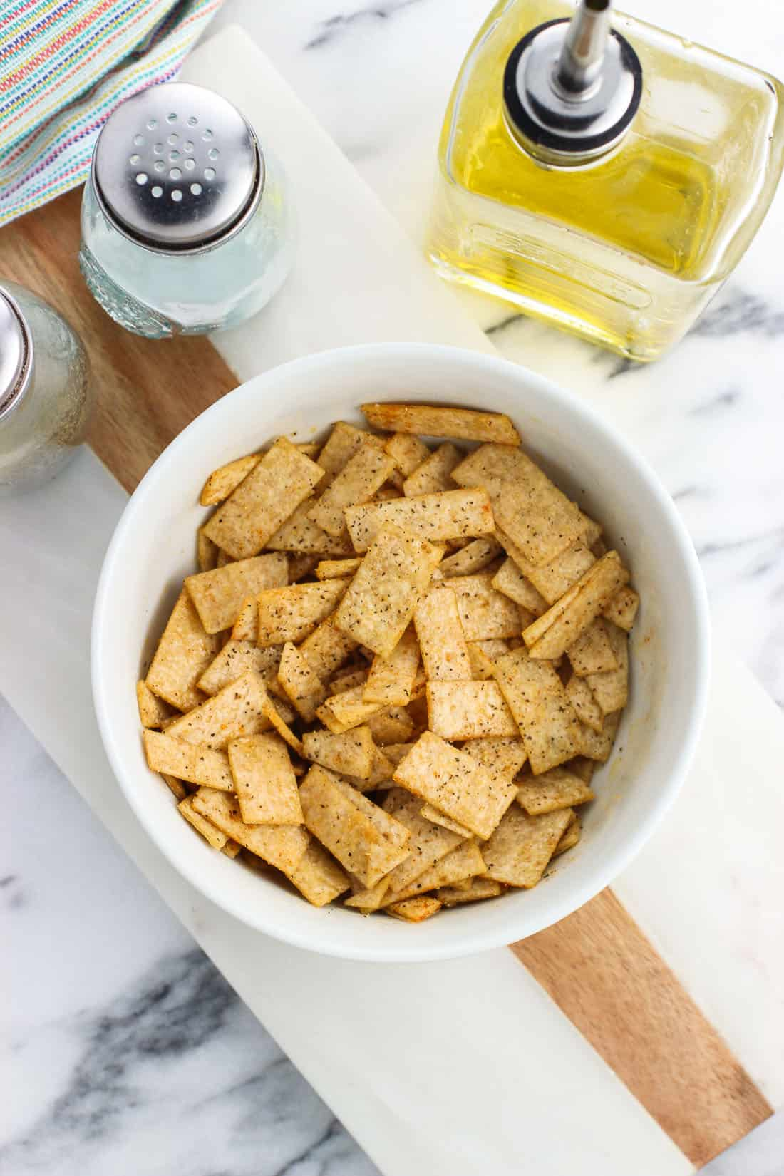 Tortilla strips in a bowl tossed with oil before being baked.