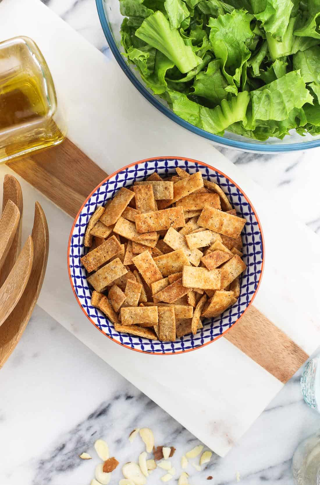 A bowl of baked tortilla strips next to a bowl fo lettuce and salad tongs.