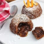Two mini lava cakes on a plate with a bite removed from the front cake to show the filling.