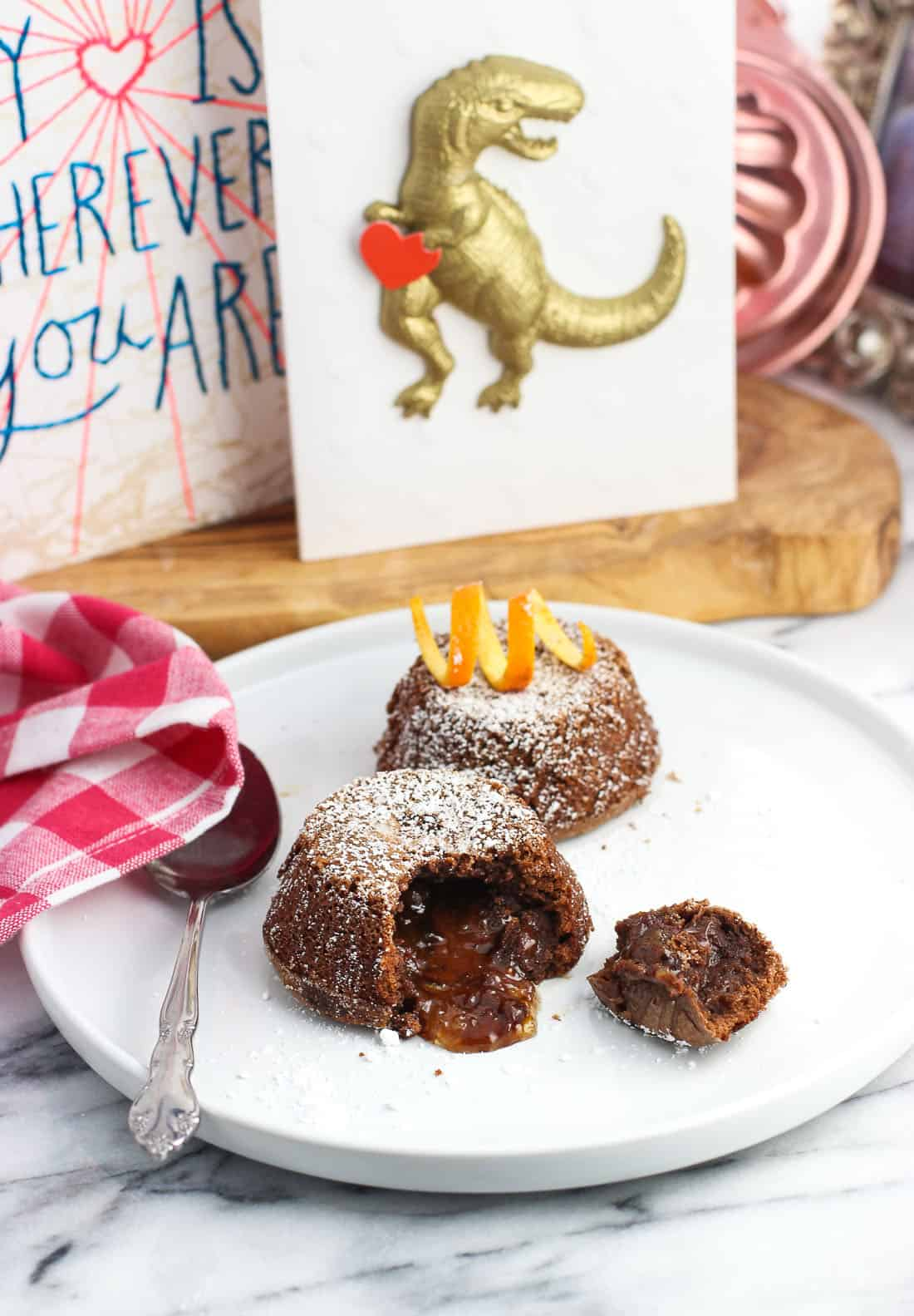 Two lava cakes on a dessert plate, one with a spoonful taken out of it to show the molten filling, with the other whole topped with an orange rind twist. Two Valentine's Day cards are displayed in the background