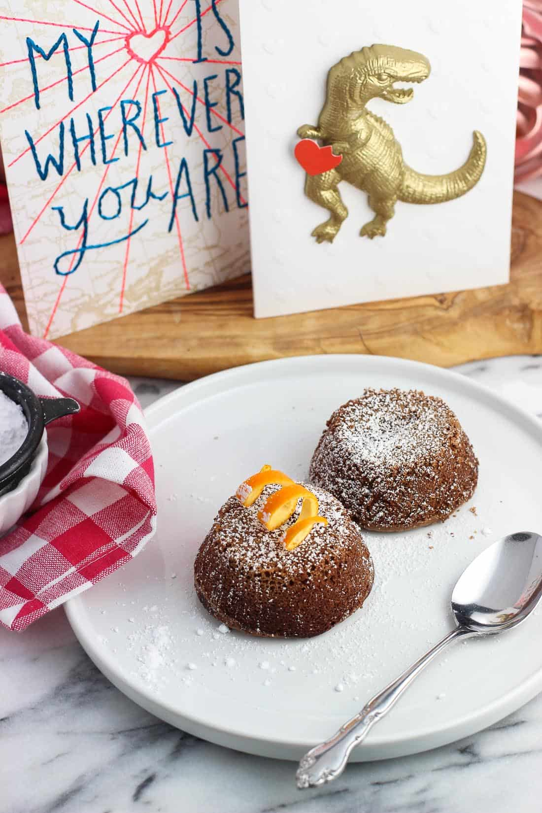 Two whole lava cakes on a plate, dusted with confectioners' sugar, with one topped with an orange peel twist. There's a spoon on the plate and two Valentine's Day cards are displayed in the background