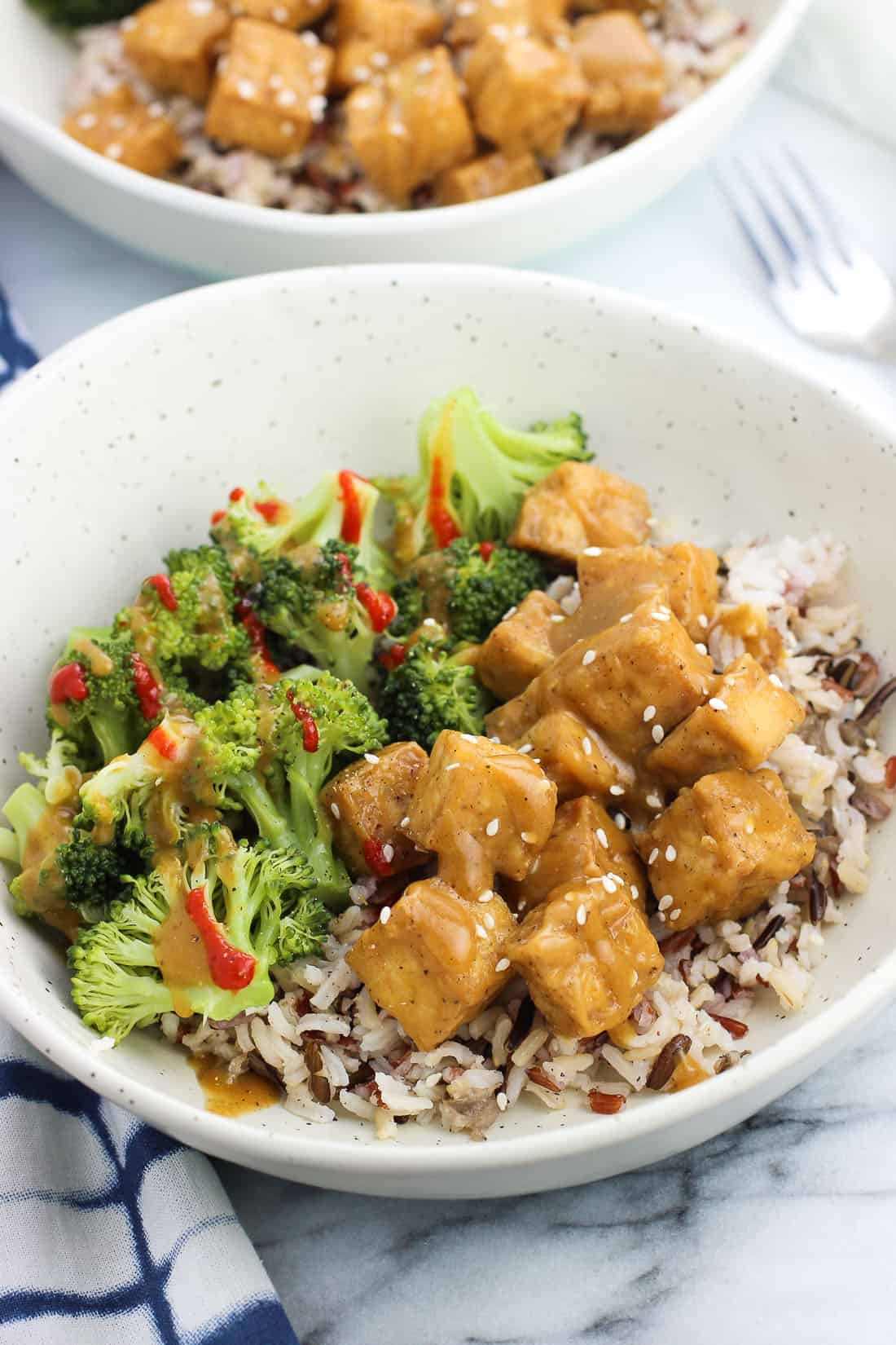 A bowl with tofu, rice, and broccoli with another bowl of the same in the background