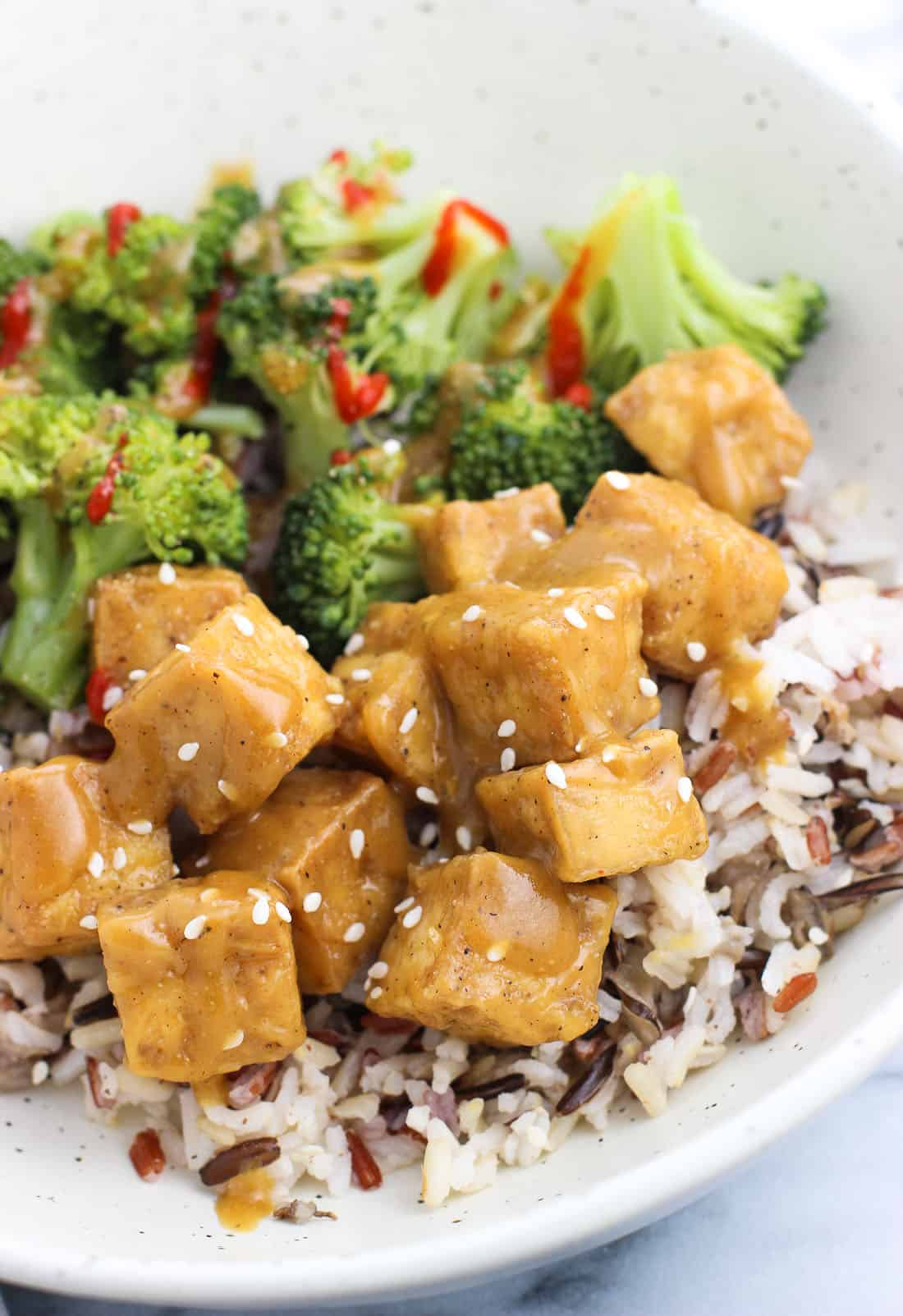 Tofu tossed in ginger sauce served over rice in a dinner bowl with a side of sriracha-drizzled broccoli