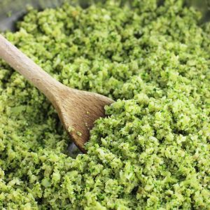 A wooden spoon scooping pesto broccoli rice in the pan