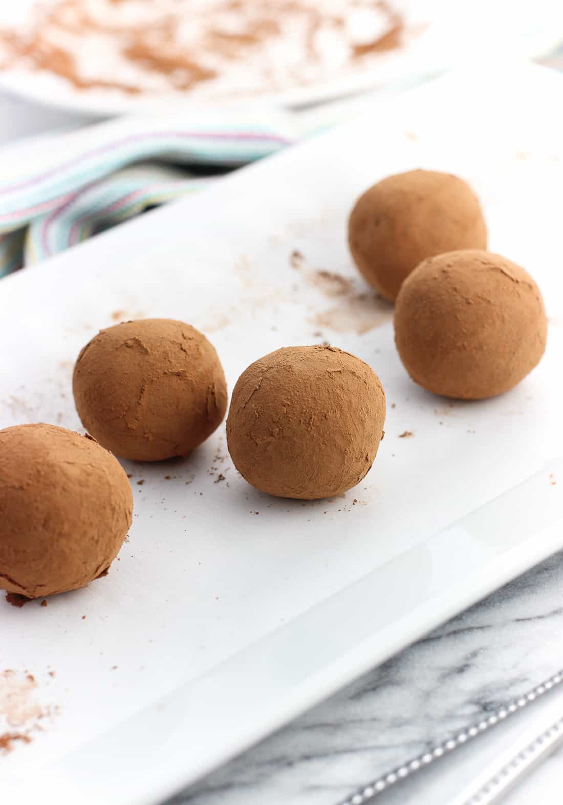 Five truffles rolled in cocoa powder on a rectangular ceramic serving tray