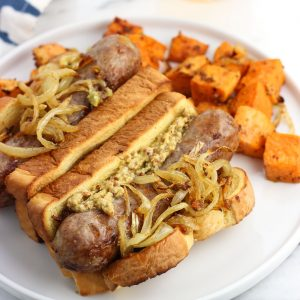 Two bratwursts in buns with the fixing on a plate with roasted sweet potatoes.