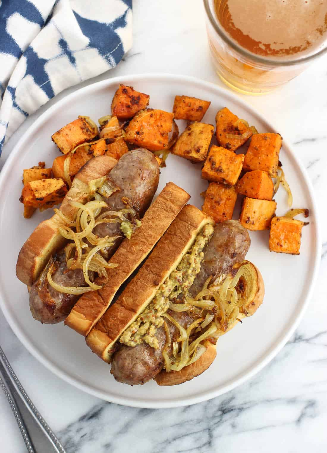 Two bratwursts and sweet potatoes on a plate next to a glass of beer.