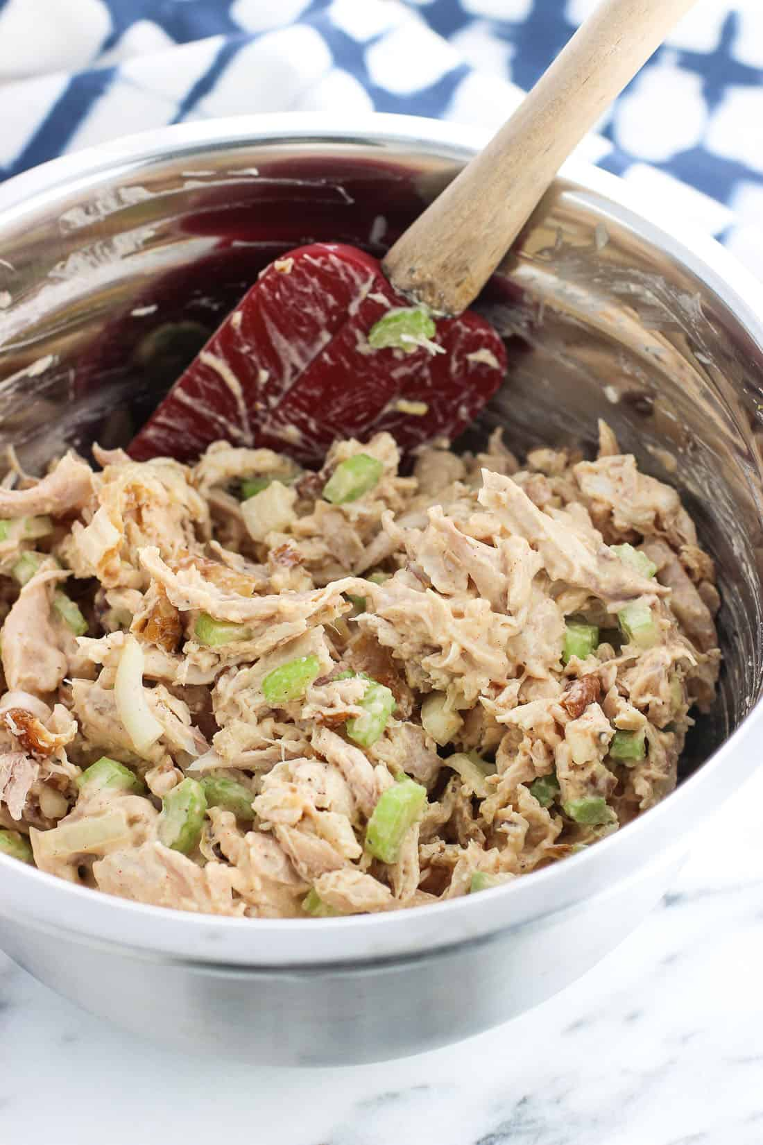 Chicken salad in a mixing bowl with a spatula