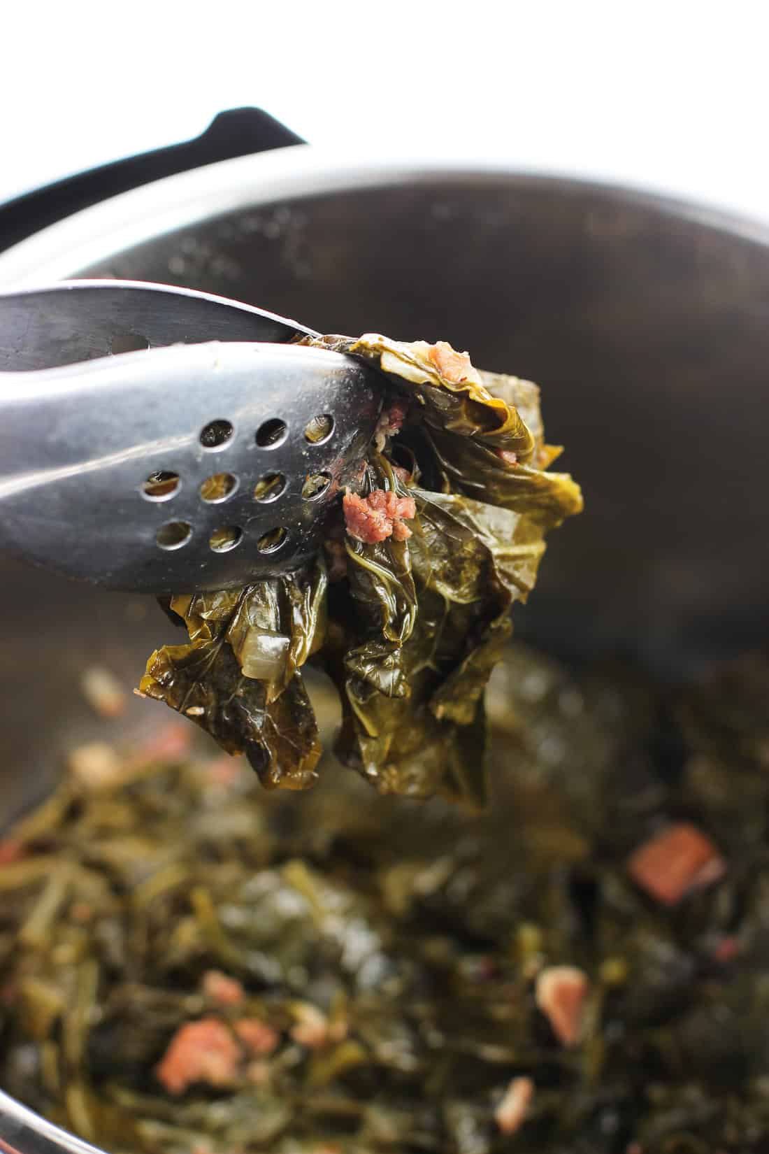 Tongs lifting collard greens out of the Instant Pot.