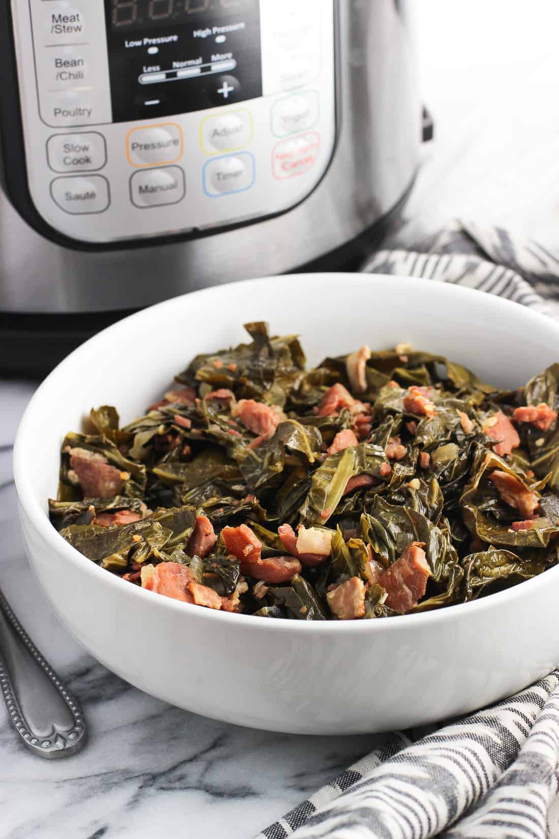 A serving bowl full of Southern collard greens with an Instant Pot in the background.