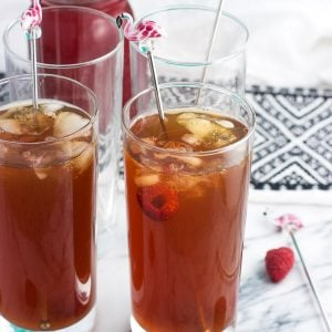 Glasses of iced tea garnished with fresh raspberries and flamingo drink stirrers.