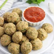 Turkey meatballs piled on a plate with a small bowl of marinara dipping sauce.
