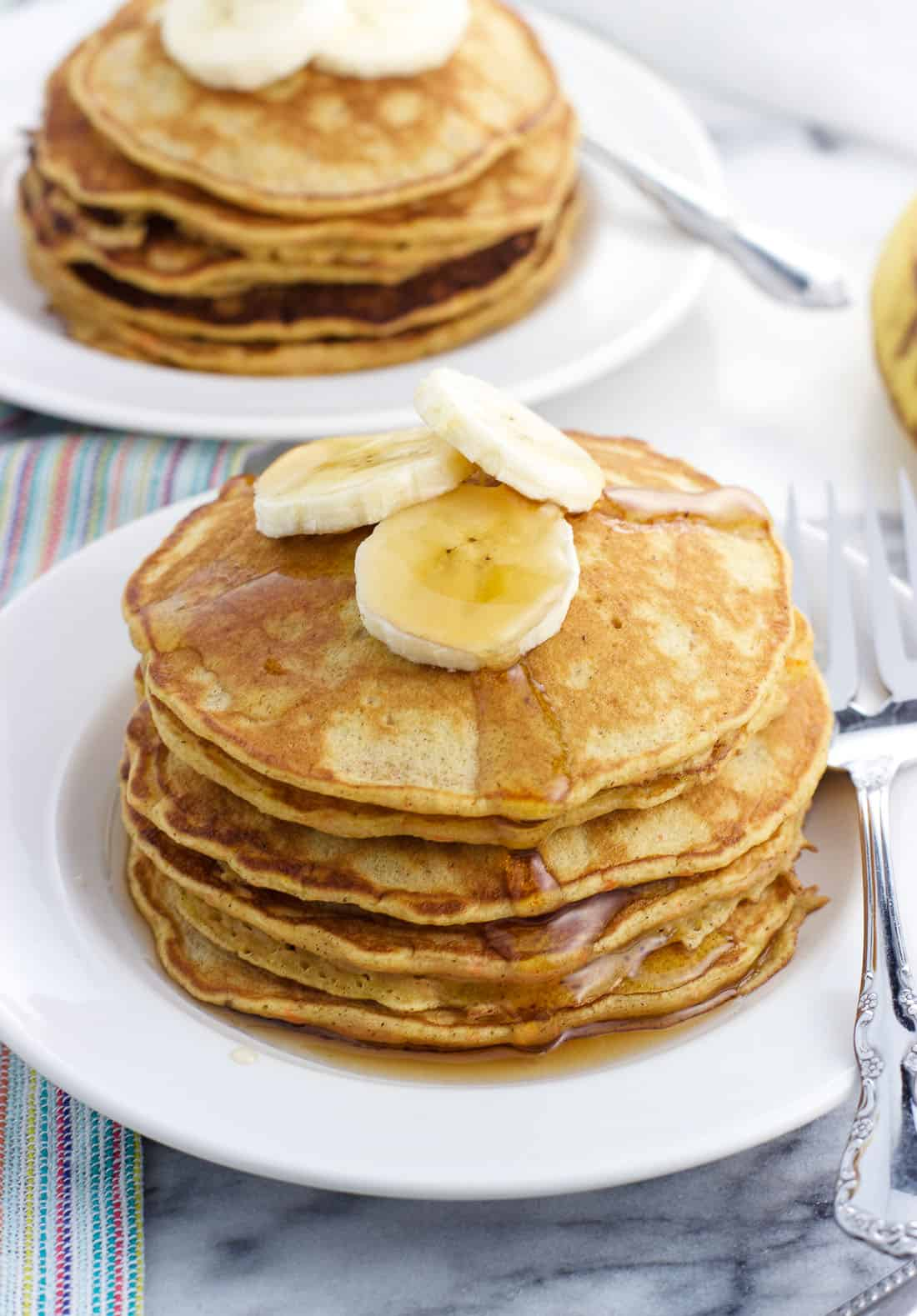 A stack of pancakes topped with maple syrup and banana slices on a small plate, with another plate of pancakes in the background