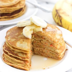 A stack of pancakes topped with banana slices on a plate with a wedge cut out.