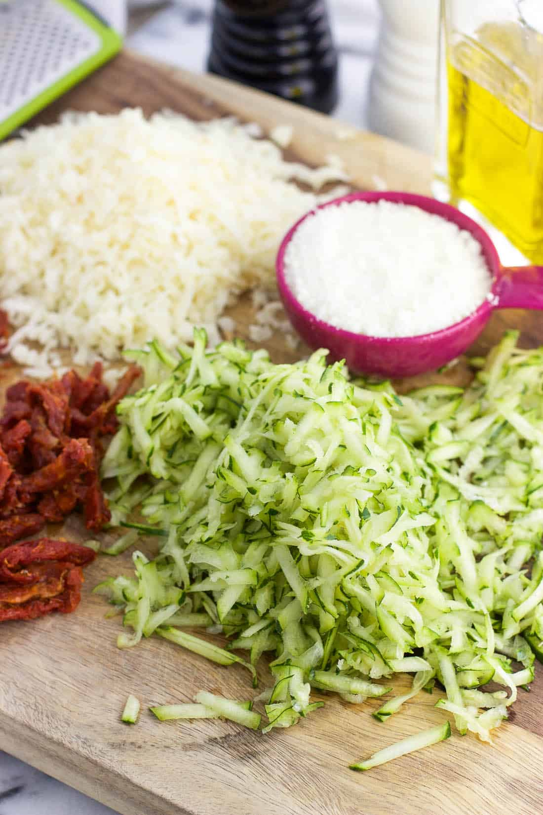 Shredded cheese, Parmesan, sun-dried tomatoes, and shredded zucchini on a wooden cutting board