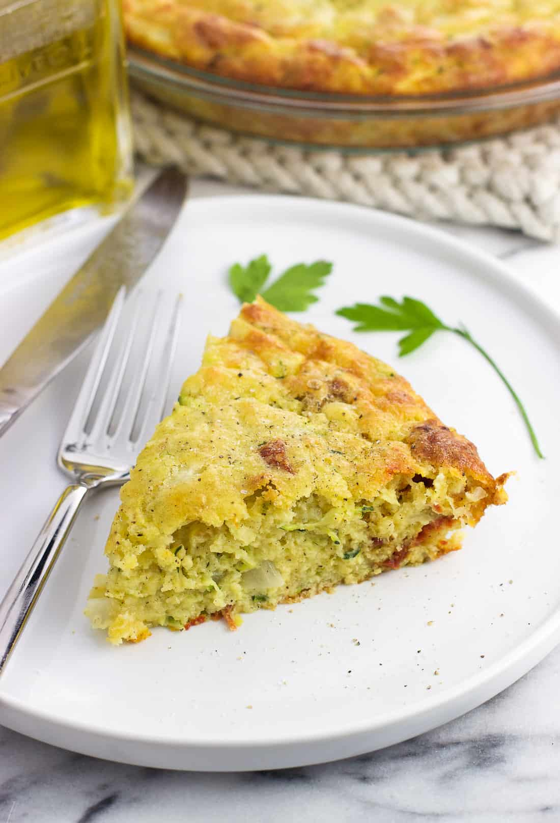 A slice of quiche on a plate with a fork and knife in front of the pan of quiche and a glass bottle of olive oil