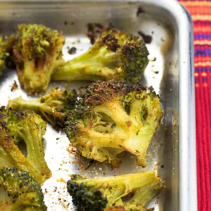 Broccoli florets on a rimmed metal baking sheet roasted and seasoned with Cajun and garlic seasonings