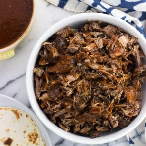 Pulled pork in a serving bowl next to a bowl of homemade BBQ sauce and warmed tortillas