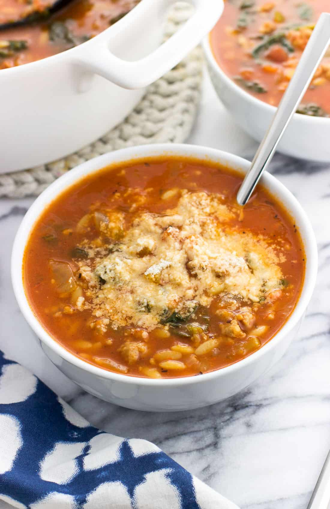 A bowl of soup topped with grated Parmesan cheese