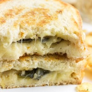 Two halves of a grilled cheese sandwich stacked on top of on another showing the melty filling