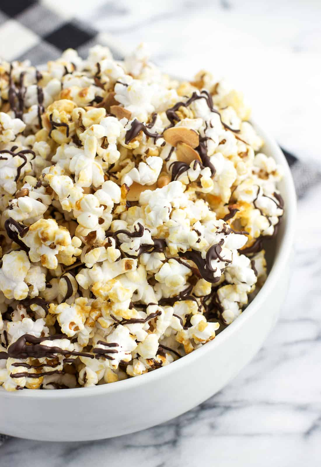 A close-up of chocolate drizzled popcorn in a serving bowl