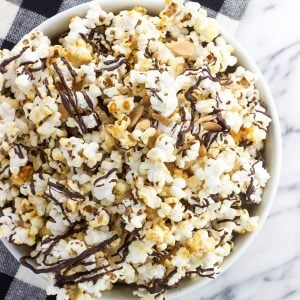 Easy homemade chocolate drizzled kettle corn is mixed with toasted almonds and topped with dark chocolate for a quick and crunchy chocolate popcorn dessert.