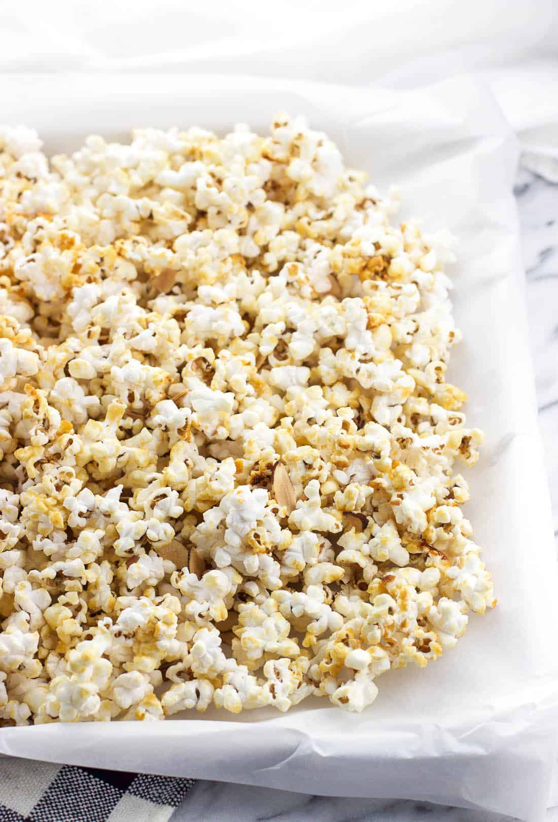 Kettle corn spread out on a parchment paper-lined baking sheet