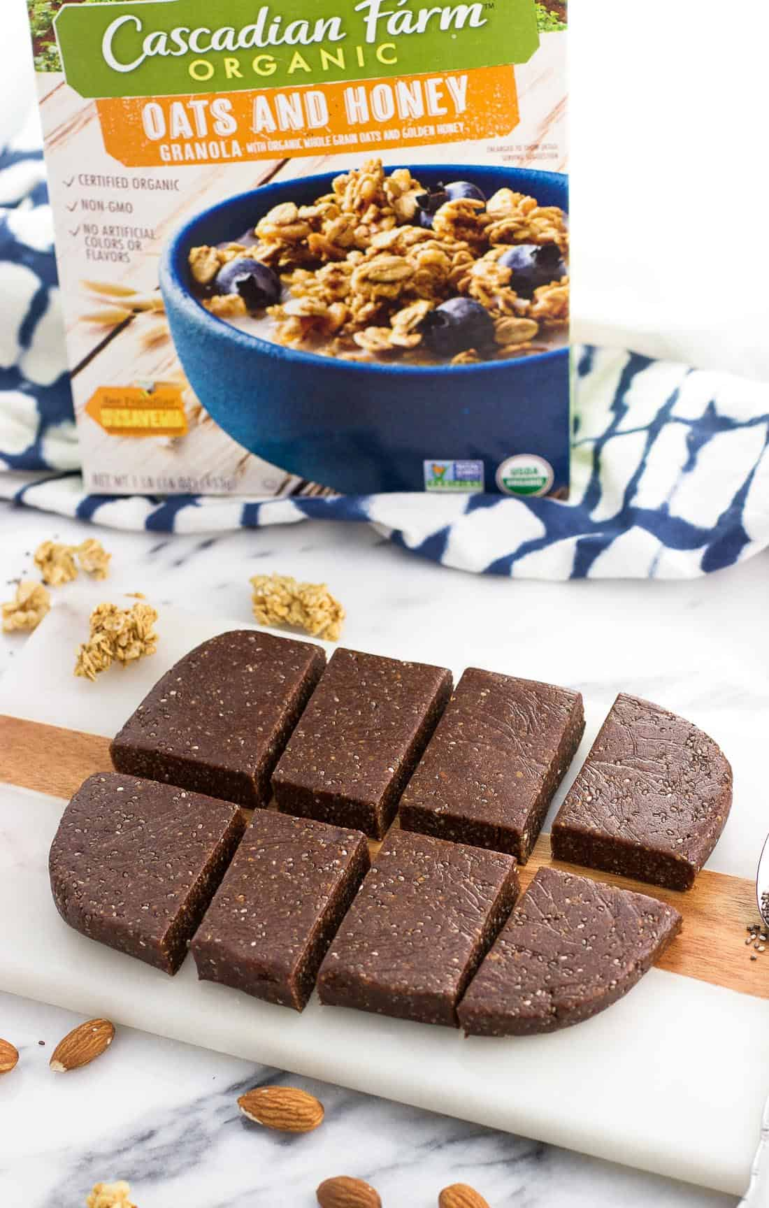 Eight sliced bars on a marble board with a box of granola in the background