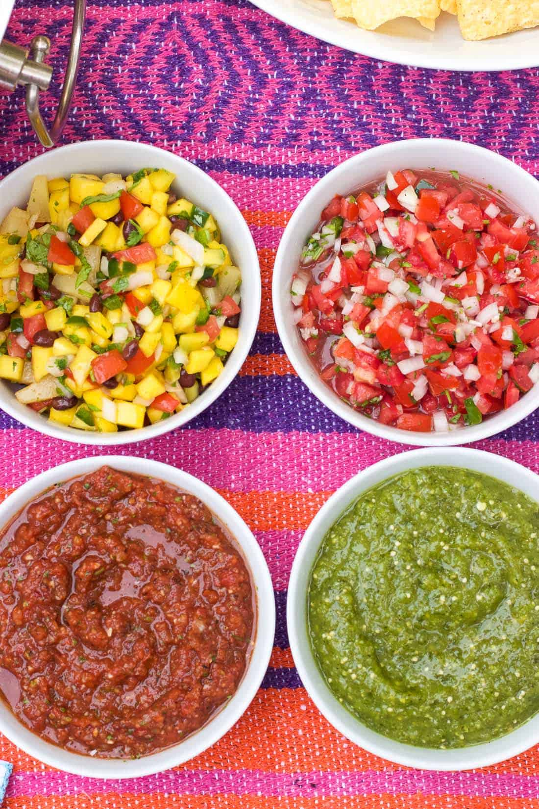 An overhead shot of four bowls of different salsas