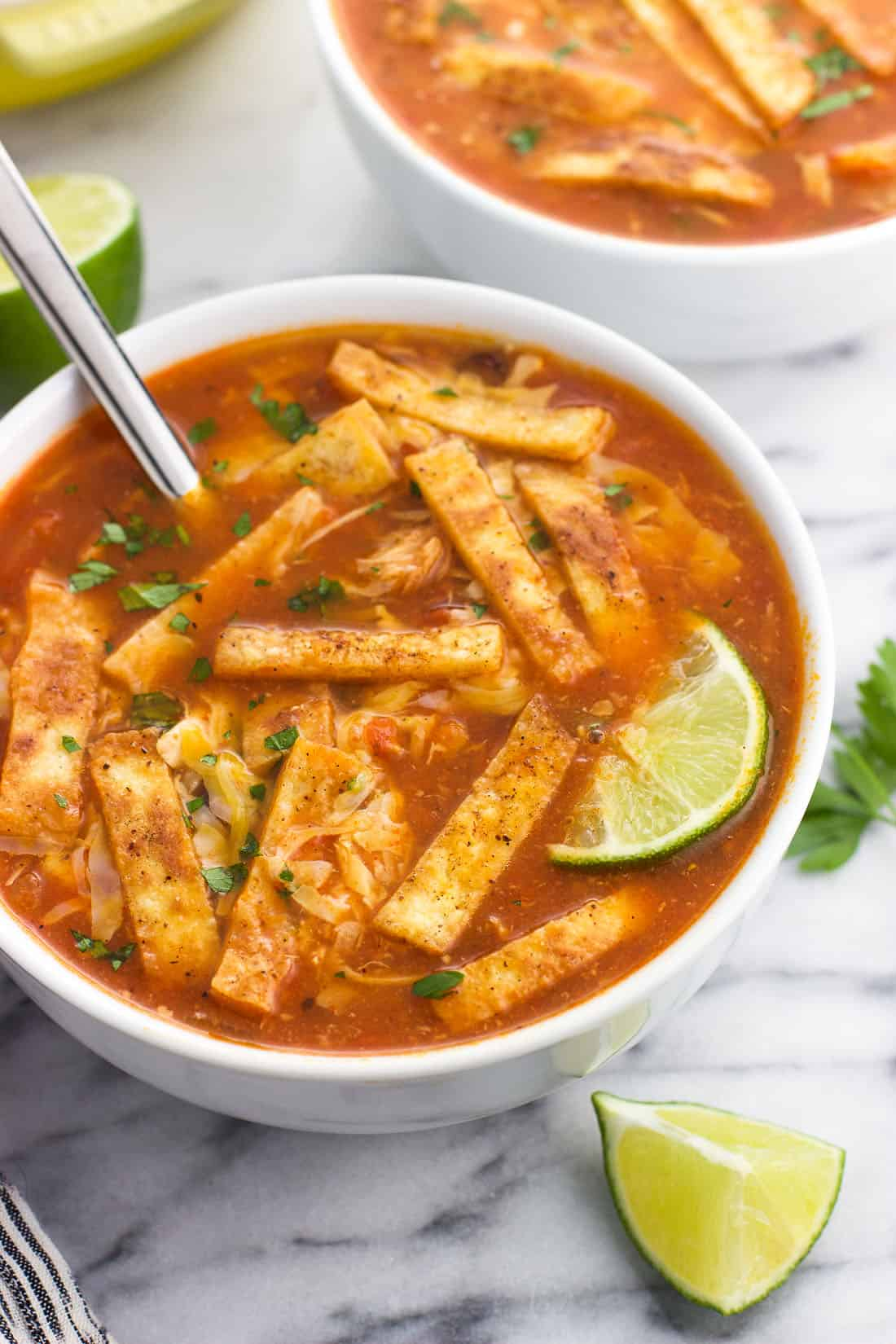 Easy chicken tortilla soup with rice is filled with bold southwestern flavors and on the table in forty minutes. Top this healthy soup recipe with tortilla strips, cheese, and a sprinkling of lime juice for a delicious main dish recipe.