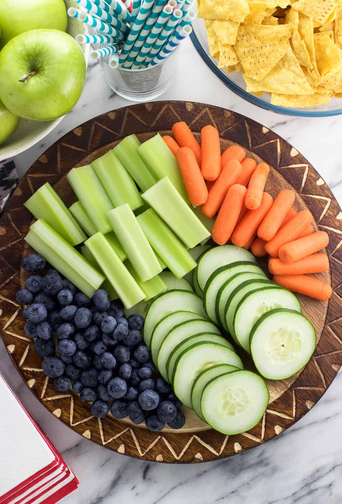 Sliced vegetables and fruit as part of a party spread.