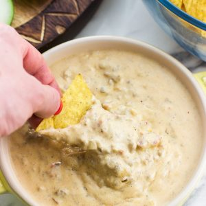 A hand dipping a tortilla chip into a bowl of beef queso dip.