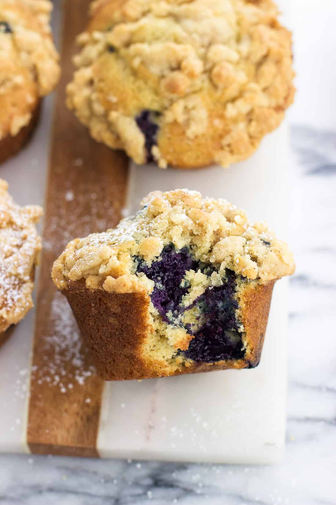 A muffin on a marble serving board dusted with powdered sugar with a big bite taken out of it