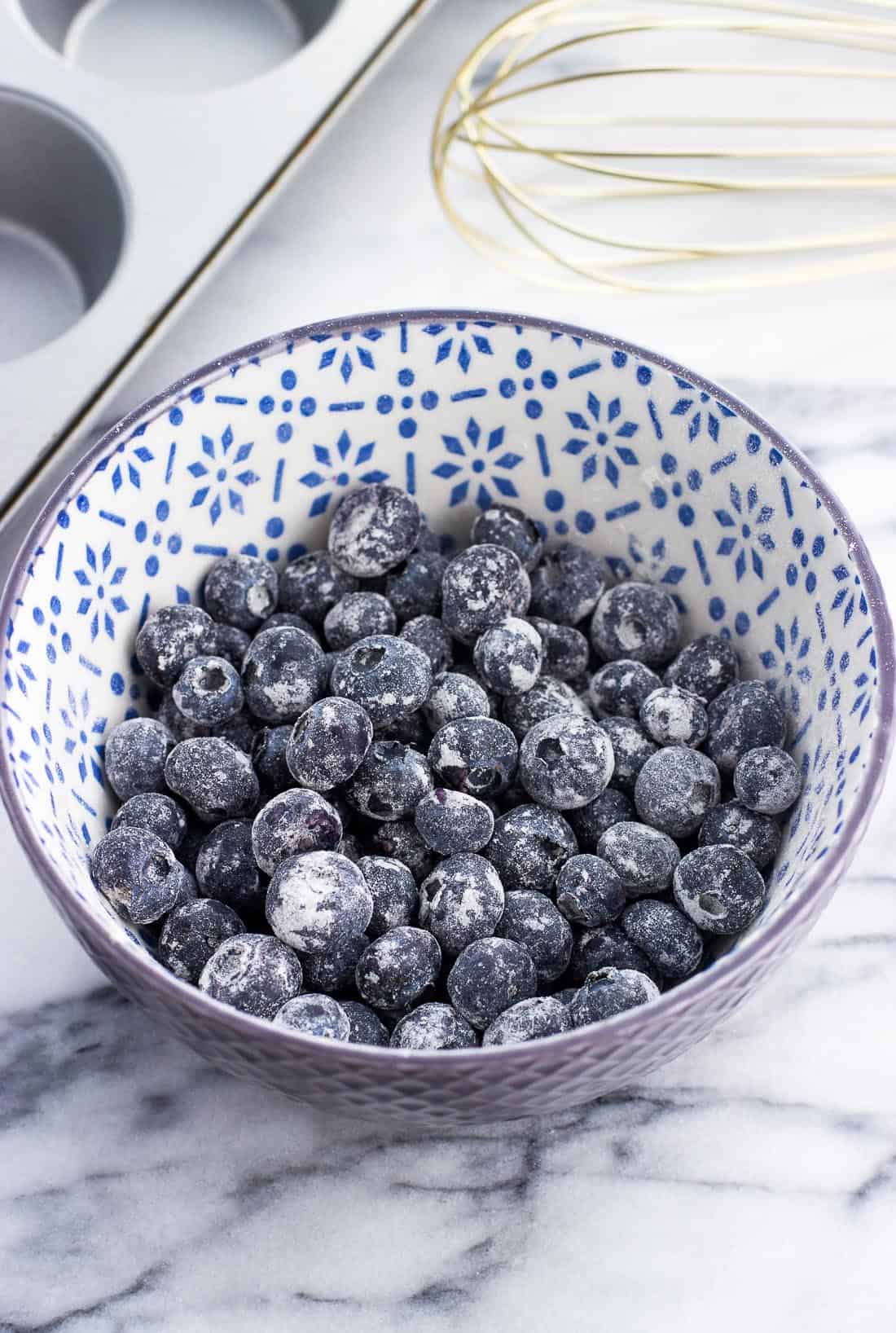 A ceramic cereal bowl filled with flour-dusted blueberries next to a muffin pan and a whisk