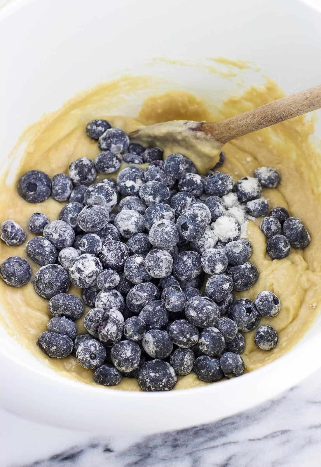 Flour-dusted fresh blueberries poured on top of muffin batter in a mixing bowl