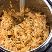 An Instant Pot filled with shredded buffalo chicken with a serving spoon.