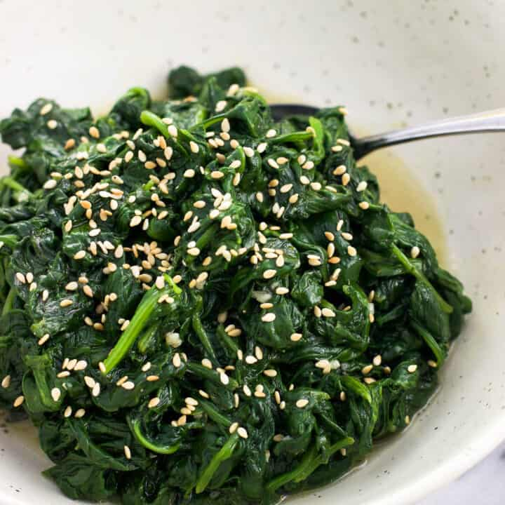 A serving dish of sauteed spinach with a spoon