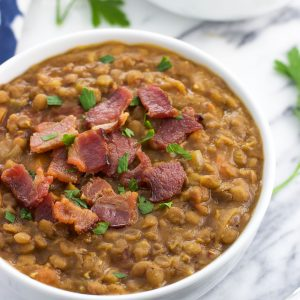 A close-up of a ceramic bowl of lentil soup topped with crumbled bacon