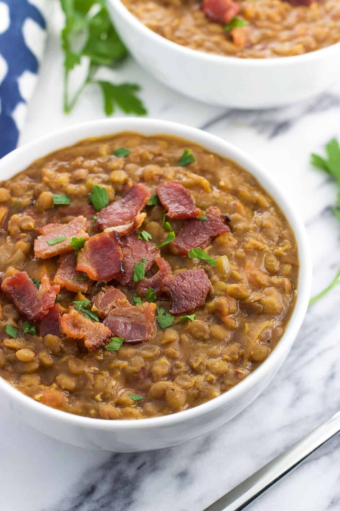 A bowl of lentil soup topped with crumbled bacon