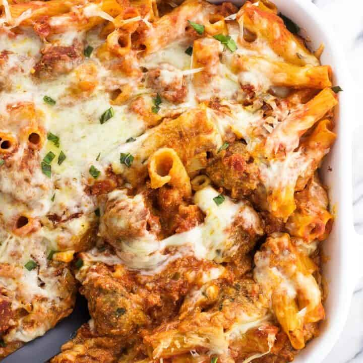 A serving spoon in a large dish of baked ziti.